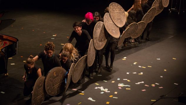 Performance of Loose Change wth giant riot shield-sized pennies by Cat Phillips at the Barbican Theatre, London, 2014