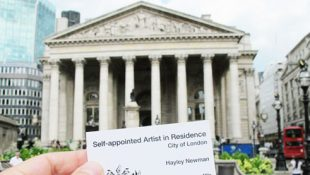 "Image of business card saying ""Self-appointed artist in residence, Hayley Newman"" being held up in front of the Bank of England"