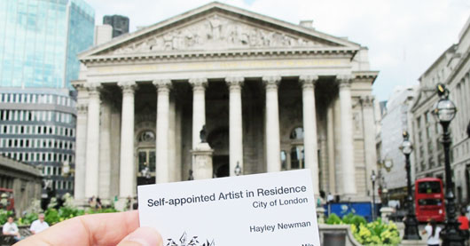 """Image of business card saying """"Self-appointed artist in residence, Hayley Newman"""" being held up in front of the Bank of England"""