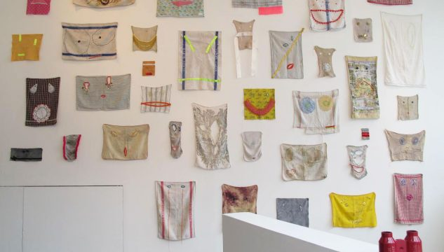 Embroidered dishcloths displayed on the wall of Castlefield Galler