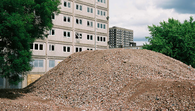 A mound of gravel outside a tower block