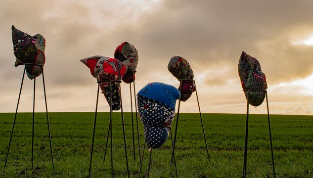 Image of cloth fetishes in a field against a dramatic sky